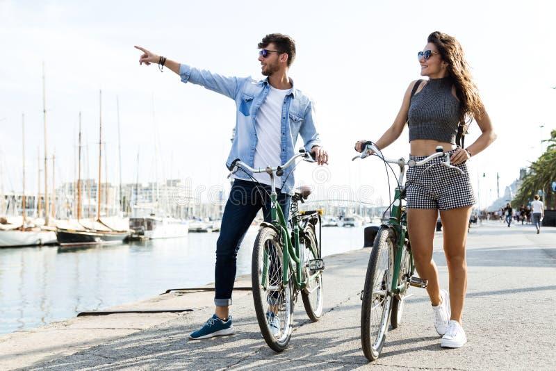 循环在城市的愉快的年轻夫妇 库存照片