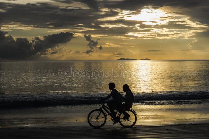 循环在日落的海滩,泰国的孩子 免版税图库摄影