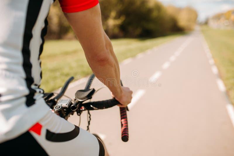 循环在柏油路的运动服的男性骑自行车者 库存图片