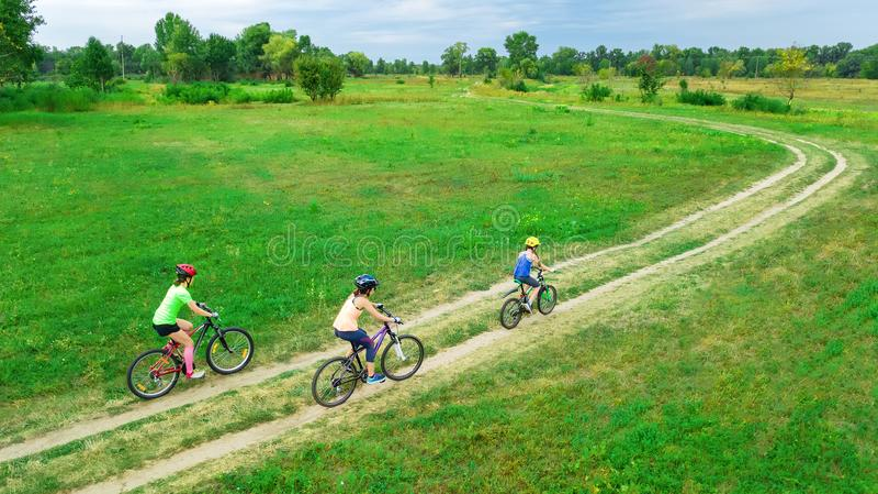 循环在自行车户外鸟瞰图的家庭从上面,有孩子的愉快的活跃母亲获得乐趣 免版税图库摄影