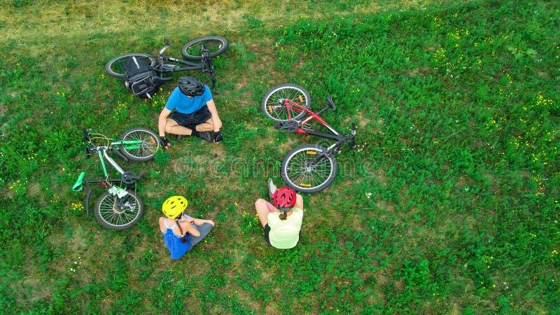 循环在自行车户外鸟瞰图的家庭从上面,有孩子的愉快的活跃父母在草,家庭体育获得乐趣并且放松 免版税图库摄影
