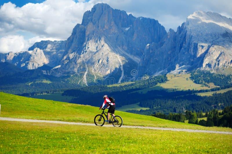 循环在Seiser Alm,最大的高处高山草甸的游人在欧洲,在背景的惊人落矶山脉 图库摄影