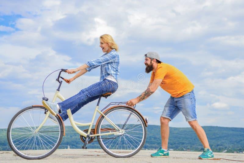 循环的女孩,当人支持她时 人帮助保留平衡乘驾自行车 循环的服务 服务和协助 技工 库存图片