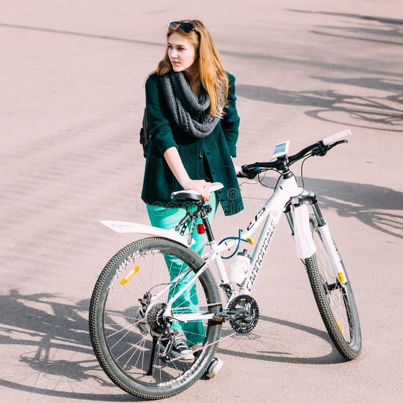 循环的季节的开头的年轻白种人女孩自行车骑士 免版税库存照片