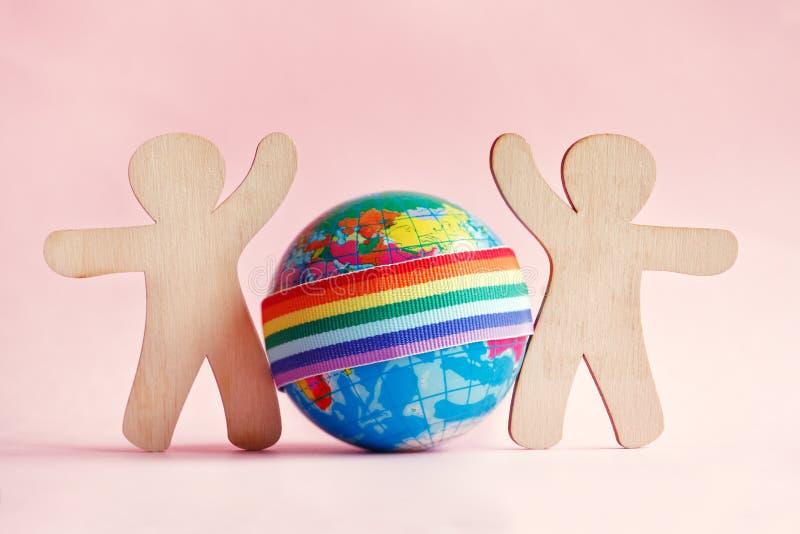 微型人和地球玩具木剪影与彩虹LGBT丝带在桃红色背景 免版税库存照片