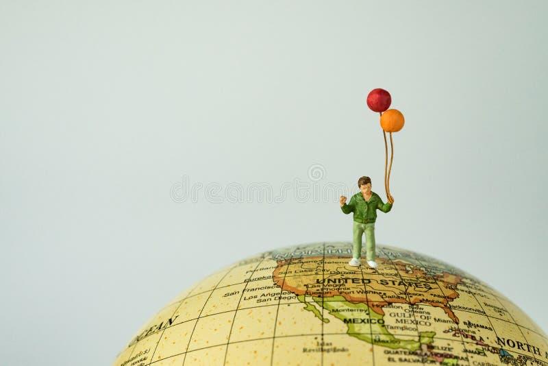 微型人民计算拿着气球替换者的愉快的孩子/男孩 免版税库存图片