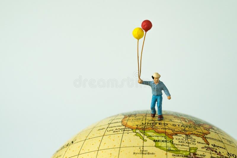 微型人民计算拿着气球的愉快的人站立在u 库存图片