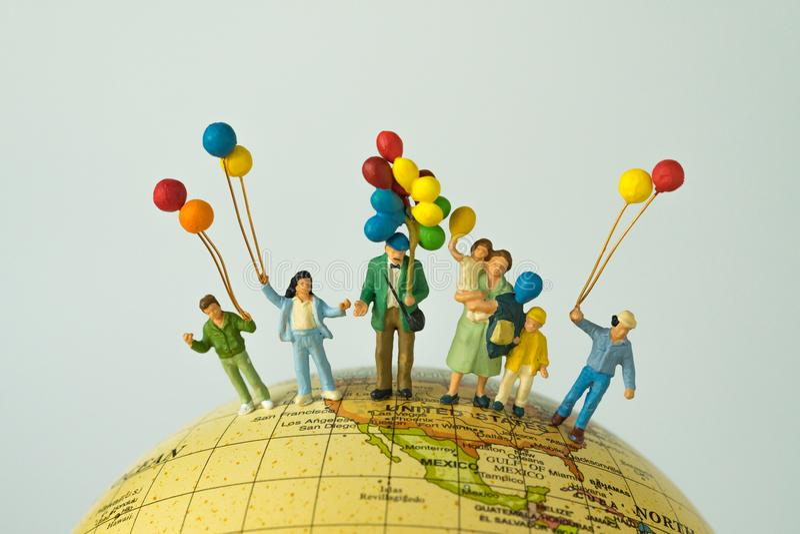 微型人民计算拿着气球的愉快的家庭站立o 库存照片