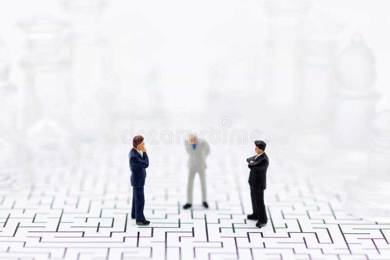 微型人民,商人在下棋比赛,分开的党,好处,用途的反面站立作为企业竞争 免版税库存照片