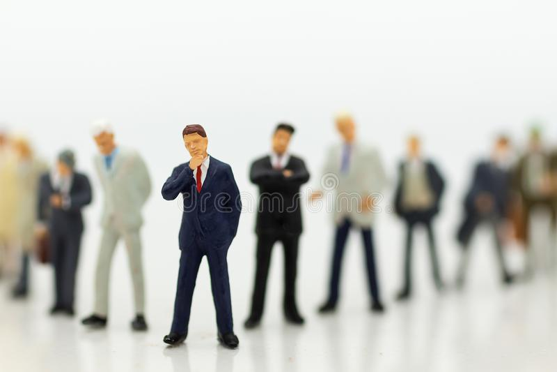 微型人民,小组商人与队一起使用,使用当适合的雇员的背景选择, 免版税库存图片