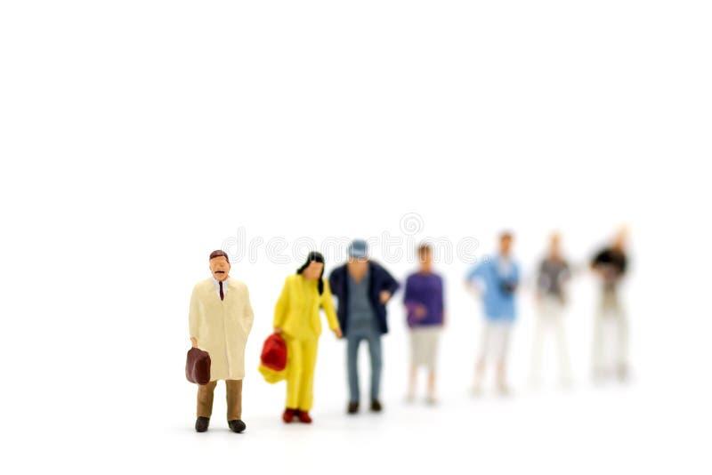 微型人民,小组商人与队一起使用,使用当适合的雇员的背景选择 免版税库存照片