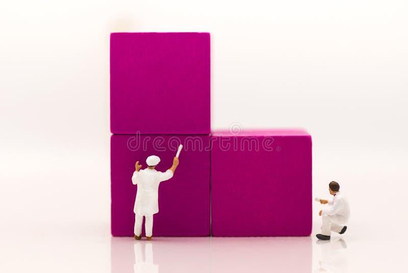 微型人民,工作者绘紫色在木立方体积木,使用当企业概念 免版税图库摄影