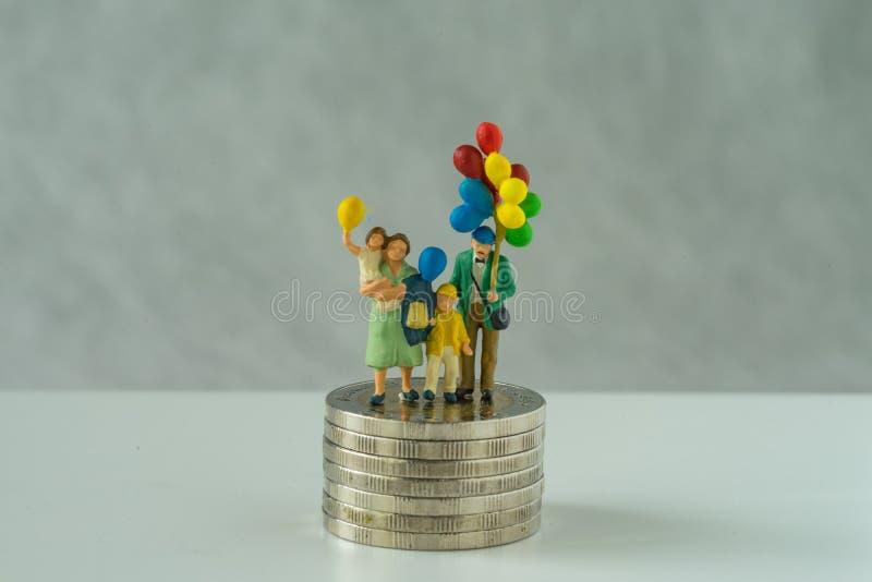 微型人民,拿着气球的家庭并肩作战在堆硬币象财政事务或愉快的退休概念 库存图片