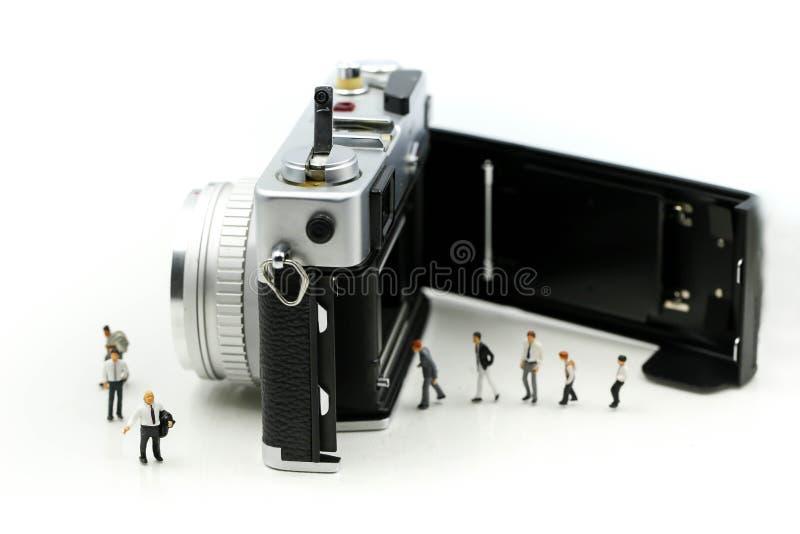 微型人民:与影片照相机,数字式事务的商人 库存图片