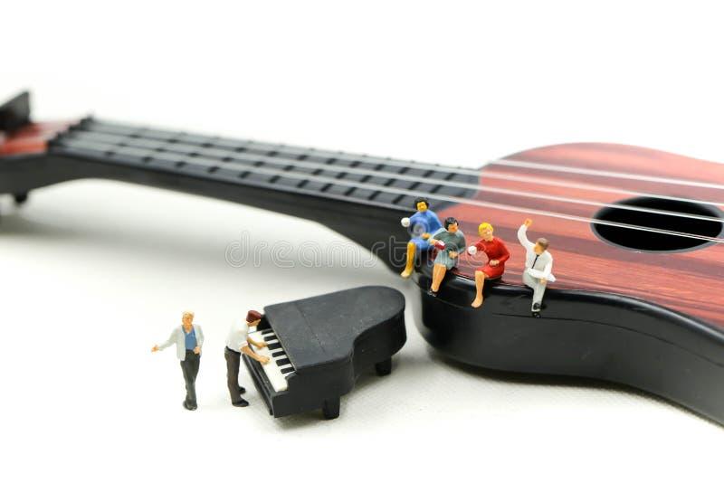 微型人民:与的人戏剧微型钢琴坐声学吉他 时期放松或音乐放松概念 免版税库存图片