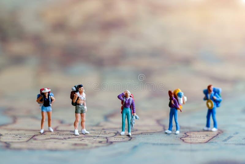 微型人民:世界地图的,旅行的概念背包徒步旅行者 免版税图库摄影