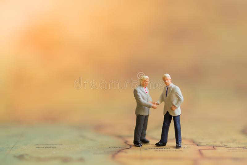 微型人民:商人做一个成交,商务伙伴会议概念 免版税库存图片