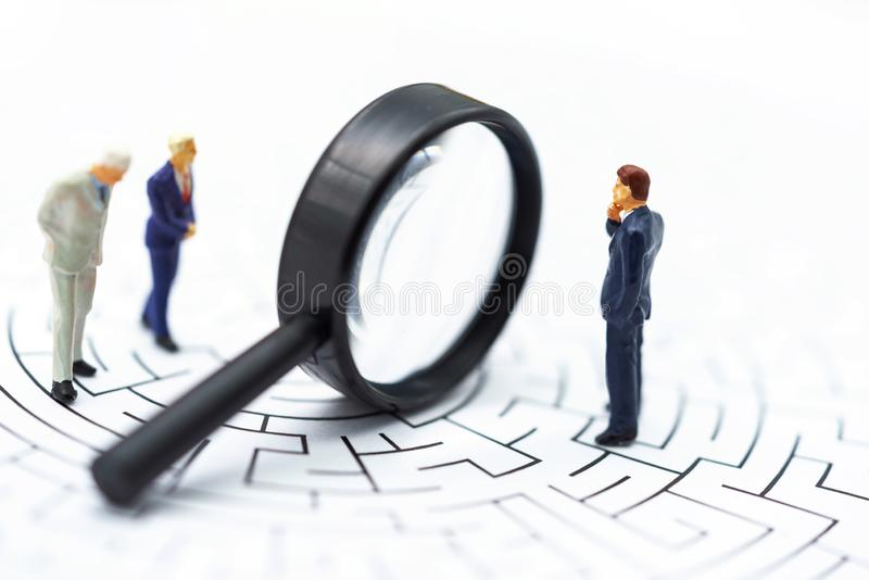 微型人民:商人发现在迷宫的路线的用途放大镜 发现解答的概念,解决问题 库存图片