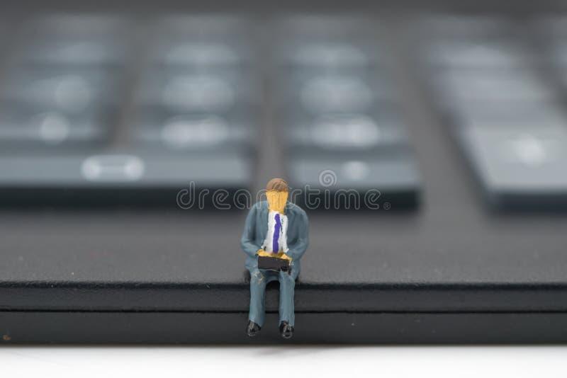 微型人民:商人坐计算器 库存图片