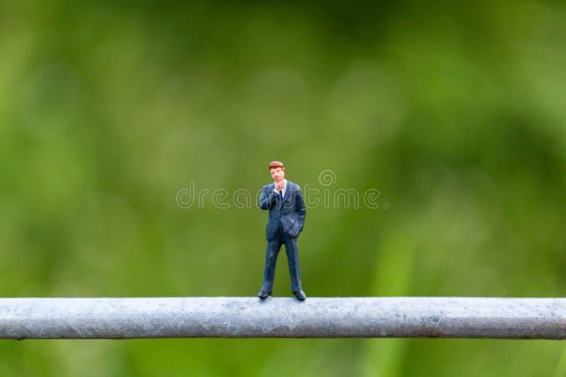 微型人民:在一根导线的商人立场有绿色背景 图库摄影