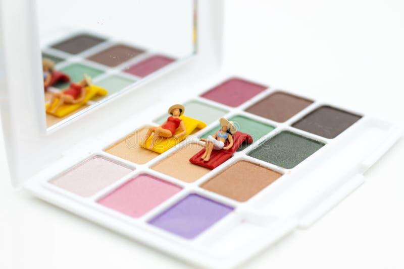 微型人民:在五颜六色的眼影膏的妇女谎言 秀丽的图象用途,化妆产品 库存图片