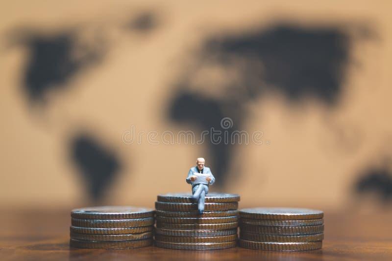 微型人民:在堆的商人硬币、金钱和financ 库存照片