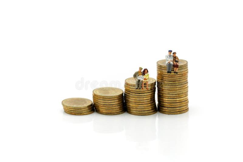 微型人民:多年龄坐堆硬币, busines 免版税库存图片