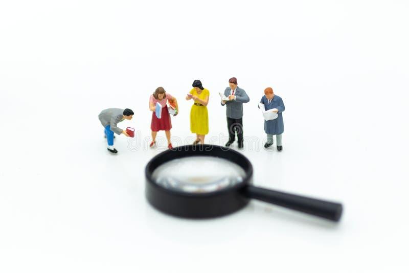 微型人民:学生读了与放大镜的书 教育概念的图象用途 免版税库存图片