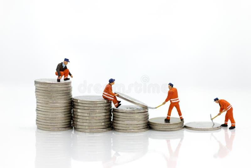 微型人民:工作在堆硬币,从工作的收入的工作者 企业概念的图象用途 库存照片
