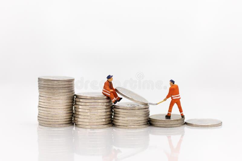 微型人民:工作在堆硬币,从工作的收入的工作者 企业概念的图象用途 免版税库存照片