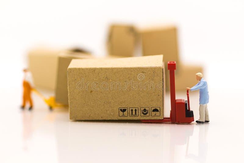 微型人民:工作者用途有箱子的码垛车使用当仓库概念的背景事务 免版税库存图片