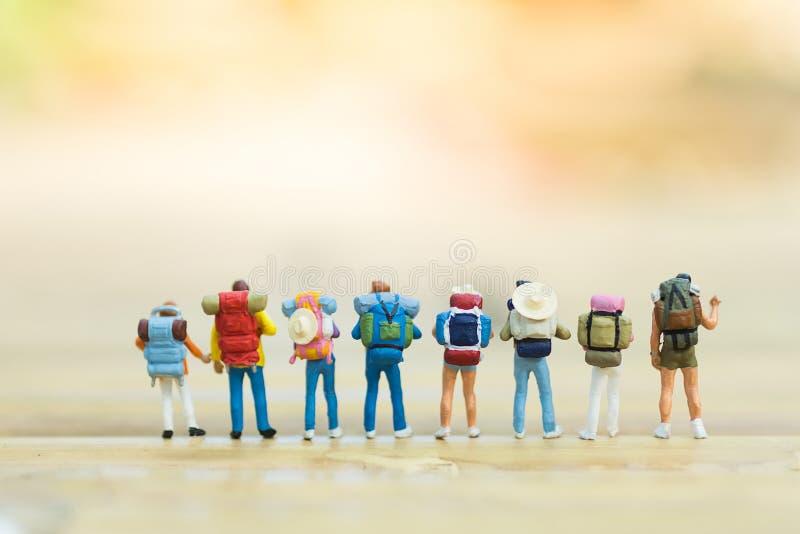 微型人民:旅行的背包徒步旅行者以一团队,使用作为trav 免版税库存图片