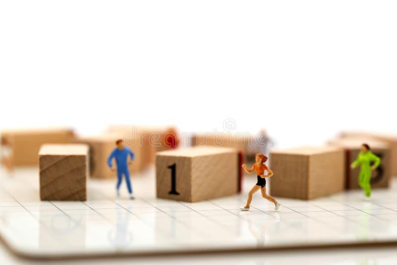 微型人民:有数字木块的马拉松运动员, 免版税库存照片