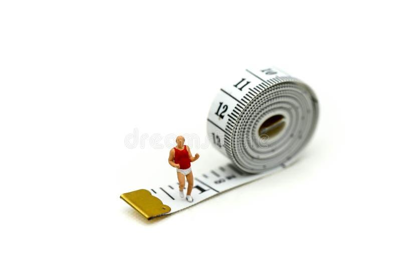 微型人民:有测量的磁带的马拉松运动员,跑步 库存图片