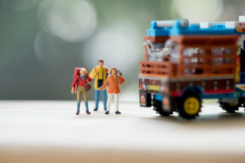 微型人民:有背包身分的旅客在泰国种田的卡车旁边 搭车概念 库存照片