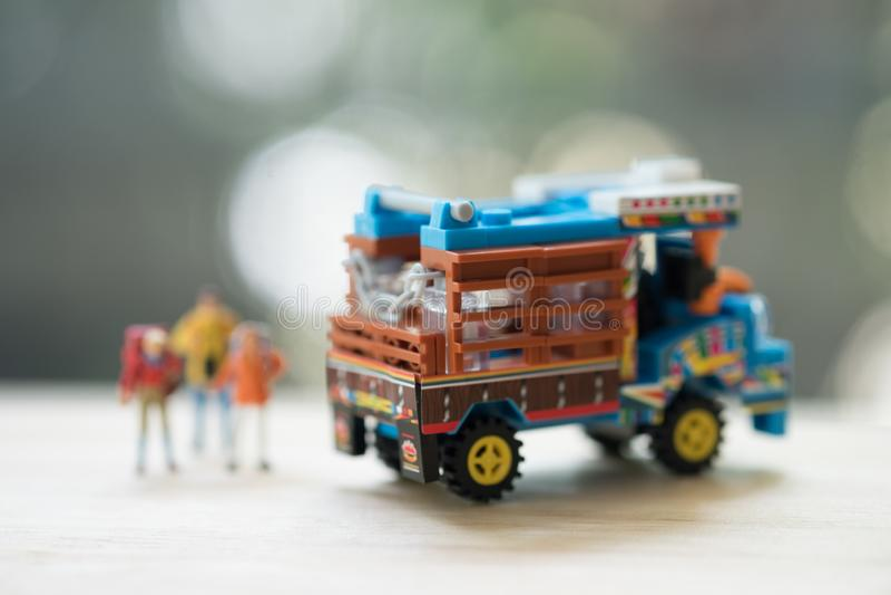 微型人民:有背包身分的旅客在泰国种田的卡车旁边 搭车概念 免版税库存照片