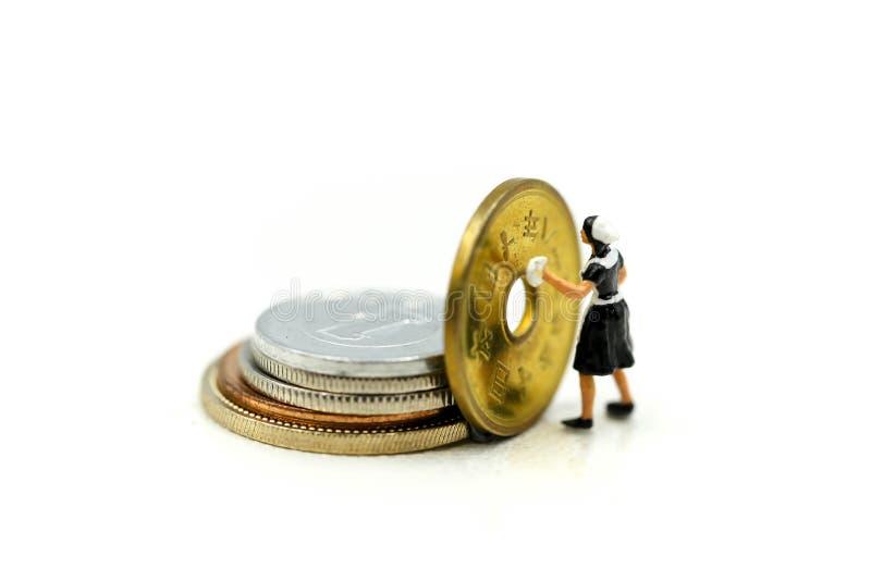 微型人民:清洗金黄硬币的工作者和佣人 Busines 库存图片