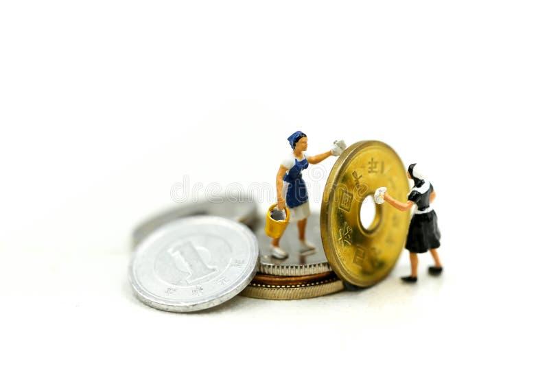 微型人民:清洗金黄硬币的工作者和佣人 Busines 库存照片