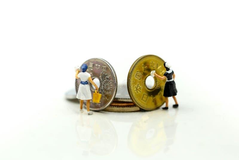 微型人民:清洗金黄硬币的工作者和佣人 Busines 免版税库存照片