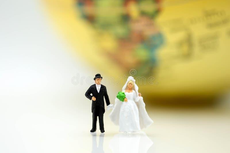 微型人民:爱夫妇站立与地球世界地图ballo 库存图片