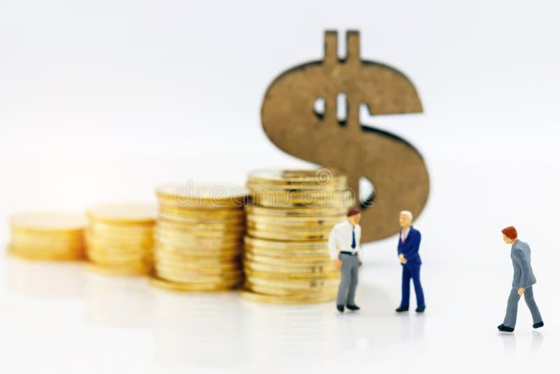 微型人民:站立与硬币堆和玩偶的商人 免版税库存照片