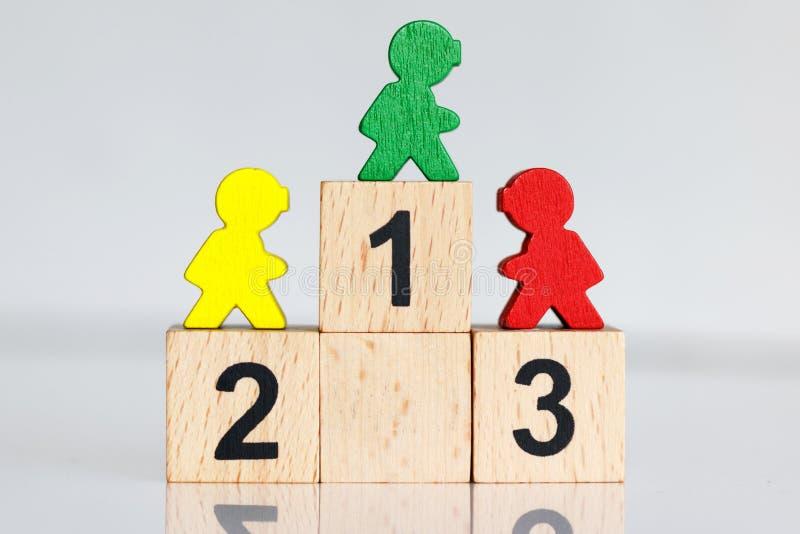 微型人民:站立五颜六色的图在有企业队的木指挥台1,2,3 免版税库存图片