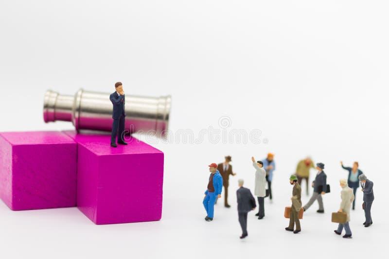 微型人民:站立在与双筒望远镜的木刻的商人 适合的雇员的选择的, HR, HRM图象用途, 免版税库存图片