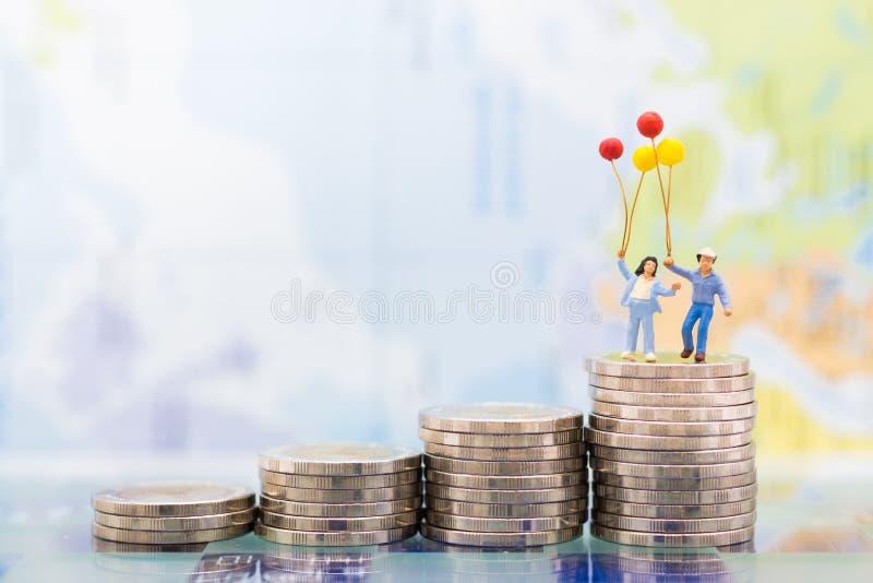 微型人民:站立在堆的孩子与气球的硬币 健康保险的孩子的,企业概念图象用途 免版税图库摄影