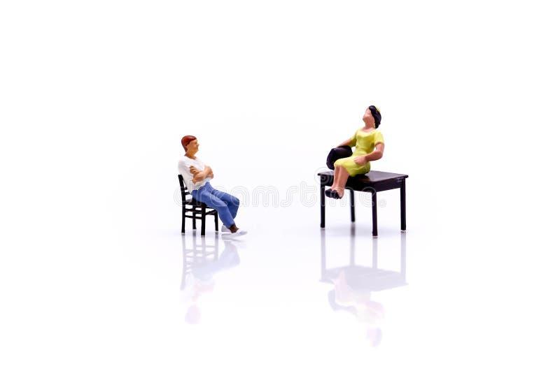 微型人民:谈话和坐与椅子的爱夫妇 免版税图库摄影