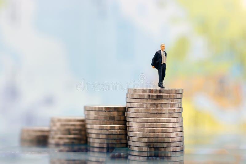 微型人民:走在硬币金钱上面的商人  免版税库存图片