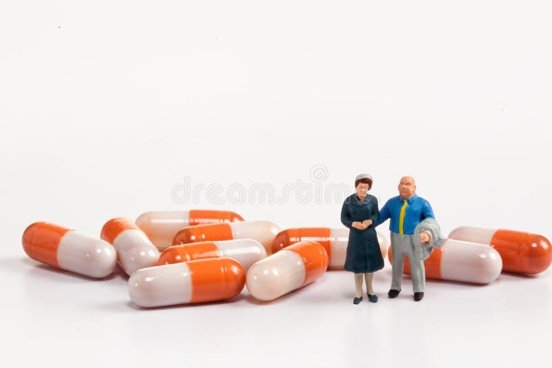 微型人民-摆在药片前面的老年人 免版税库存照片