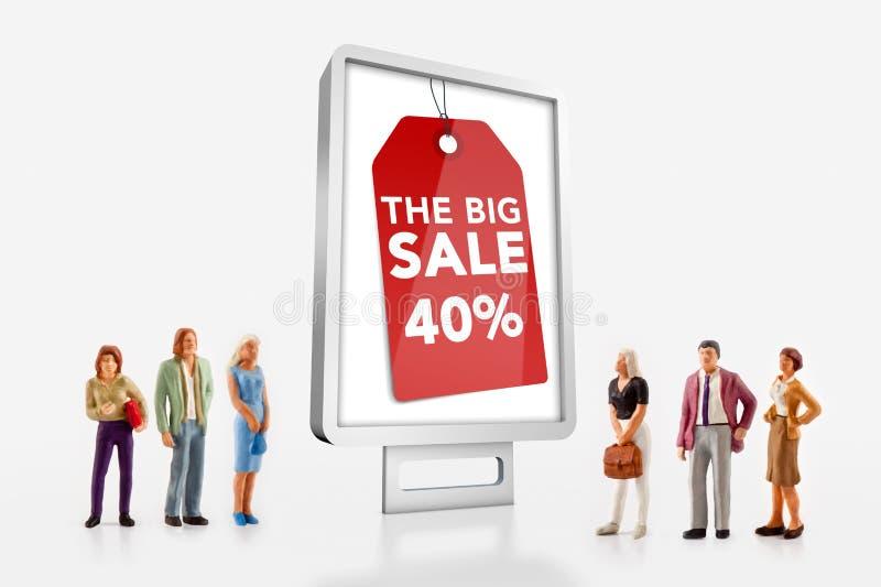 微型人民-站立在与大销售广告的广告牌前面的人们 免版税图库摄影