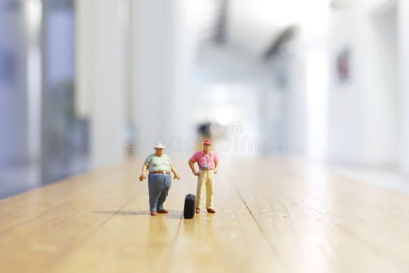 微型人:走在街道上的旅客 库存图片