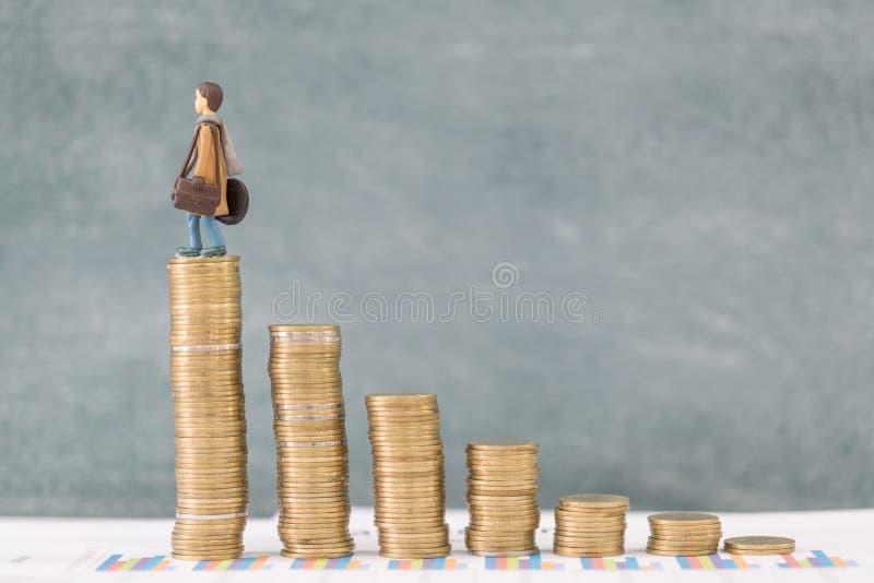 微型商人在金钱站立硬币、旅行挽救和飞行的概念 库存图片